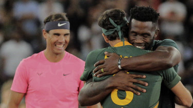 Siya Kolisi embraces Federer after presenting him with a Springboks rugby jersey.
