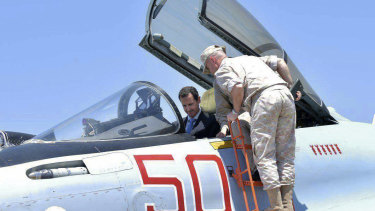 Syrian President Bashar Assad climbs into the cockpit of a Russian SU-35 fighter jet as he inspects the Russian Hmeimim air base in the province of Latakia, Syria in 2017.