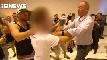 Senator Fraser Anning reacts to being egged from behind during a media conference.