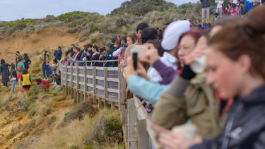 Tourists pose for photos outside the designated viewing area for the Twelve Apostlesat Port Campbell.  But the coronavirus pandemic has brought tourism to a halt.