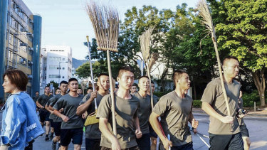 People's Liberation Army soldiers, with brooms, arrive to clean up the protest area at Hong Kong Baptist University in Hong Kong, on Saturday.