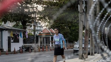 Thai woman walks past razor wire set up in front of the Crown Property Bureau on November 24, 2020 in Bangkok, Thailand. Thailand's authorities strengthened barricades around the Crown Property Bureau, a day ahead of a planned demonstration by pro-democracy protesters at the same location - the latest escalation in weeks of tumult sweeping the Thai capital. (Photo by Lauren DeCicca/Getty Images)