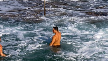 People enjoying a cold swim and watching the big surf at Bondi Beach. 30th May 2021. Photo: Edwina Pickles / SMH