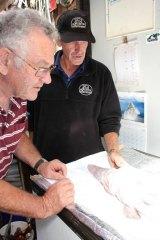 The Sapphire Coast Marine Discovery Centre's Alan Scrymgeour, left, and the Wharf Aquarium's Michael McMaster examine the goblin shark.