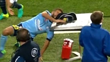Lucky escape: Sydney FC player Michael Zullo crashes into the sideline table.