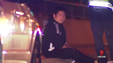 Kevin Pua sits beside the road where his sister Carmen fell from his car, suffering fatal head injuries.