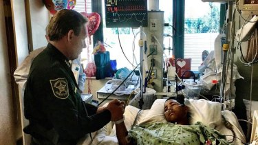 Sheriff Scott Israel, holding the hand of Anthony Borges, 15, a student at Marjory Stoneman Douglas High School. The teenager was shot five times.