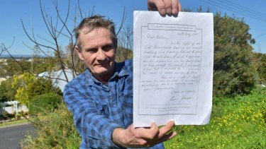 Alan Rowe holding a handwritten letter from the priest he accuses of abusing him in the 1970s that asks for forgiveness.