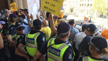 Police linked arms on the steps of Parliament to keep the taxi protesters at bay.