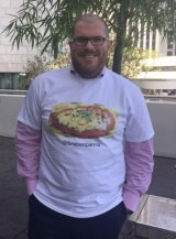"""Stephen Humphreys is searching for """"Brisbane's Best Parma"""". He is pictured in a shirt made for him as a Secret Santa present."""