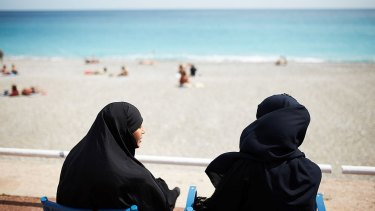 Muslim women watch sunbathers on the beach in Nice, France.