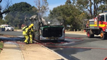 Firefighters attend to the burnt out bus.