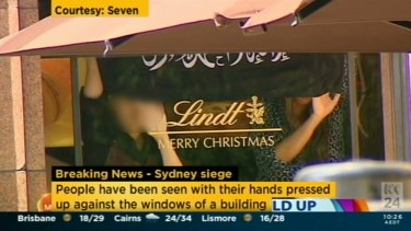 A screenshot from Channel Seven, showing hostages in the Lindt cafe