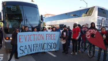An anti-eviction protest surrounds an Apple shuttle bus in San Francisco.