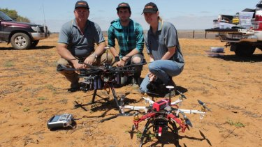 Drone owner Warren Abrams, left, with unidentified staff members.