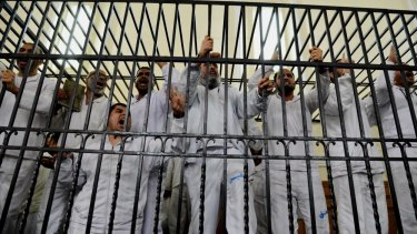 Supporters of Egypt's ousted President Mohmmed Morsi charged with violence during a trial in court in Alexandria in 2014.
