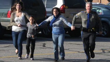 A police officer leads two women and a child from Sandy Hook Elementary School in Newtown, Connecticut, where a gunman opened fire, killing 26 people, including 20 children.