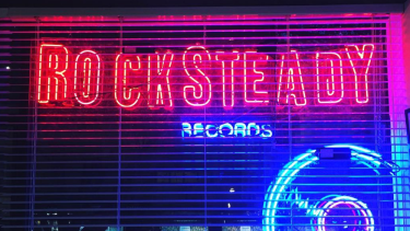 A neon sign beckons music lovers to Rocksteady Records in Melbourne.