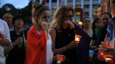 French students Marie Mailys Blasco, left, and Peyro-Saint-Paul join a large crowd in King George Square in solidarity with the French people following the Paris attacks.
