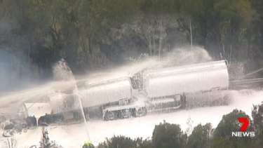 Crews from Fire and Rescue NSW spray foam on a tanker filled with ethanol.