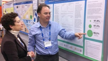 John Cook at a scientific conference in San Francisco explaining a 2013 consensus paper to Naomi Oreskes, who published a seminal work on scientific consensus.