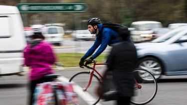 A cyclist travels down Northbourne Avenue in Braddon in peak-hour traffic.