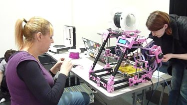 April Staines, left, and Emily Gornalle set up Staines' 3D printer.