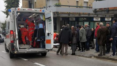 Paramedics attend to a wounded man after the shooting in Macerata, Italy.