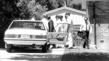 "Detective Sergeant Bob Lehman and police with the car in which Assistant Commissioner Colin Winchester was shot in his neighbour's driveway in€"" 1989."