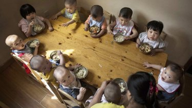 Chinese children tuck in at a foster care centre in Beijing.