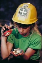 A young Leaellyn Rich holds part of the skull of a dinosaur named after her, in the mine tunnel at Dinosaur Cove, Cape Otway.