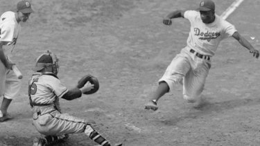 Jackie Robinson in action with his trademark home-base steal in 1948.