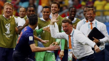 Robin van Persie rushes to celebrate with the Dutch bench after his stunning header.