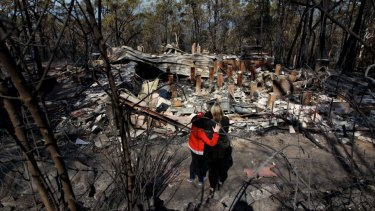 Amy Hubbard and her mum, Catherine, survey the ruins of the Winmalee home after it was destroyed during the October 2013 bushfire.