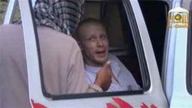 Bowe Bergdahl talks to a Taliban militant as he waits in a truck before his release.