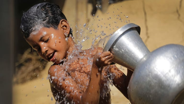 A Rohingya Muslim girl pours water on herself as she bathes outside her tent in Kutupalong Refugee camp in Bangladesh on Monday.