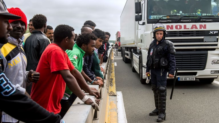 A French riot police officer stands guard as migrants wait to hide in trucks heading for England.