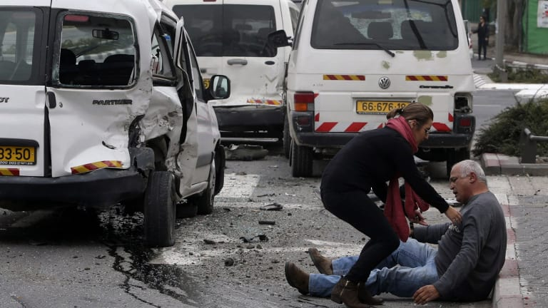 A wounded Israeli man sits on the street after Wednesday's attack by a Palestinian motorist in Jerusalem that killed one person and injured a dozen others.