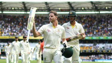 Rescue act: Steve Smith raises his bat to applause as he leaves the field at tea.