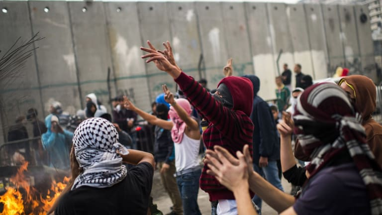 Palestinian youths clash with Israeli police in the Shuafat refugee camp, after a resident of the camp was named as the driver of the vehicle in Wednesday's Jerusalem attack.