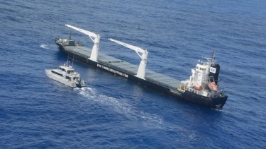 The police craft Lyle M Hoey sits alongside the cargo ship Thor Commander after its main engine broke down.