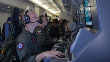 Crew members on board an aircraft P-8A Poseidon.