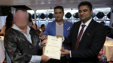 Amarjit Khela presents one of his students with a diploma.