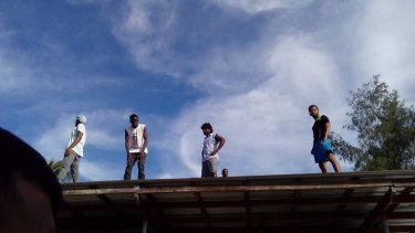 Refugees scaled the roof of a compound inside the decommissioned detention centre as police entered.