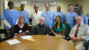 UC Berkeley Professor William Drummond (with glasses standing in centre) at the offices of the San Quentin News with inmate editors (standing) and (seated) civilian advisers.