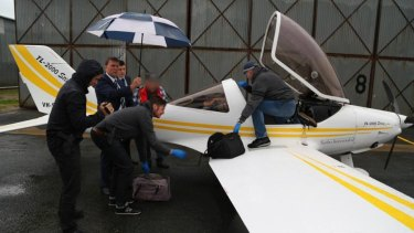 Police unload bags from the plane at Deniliquin airport.