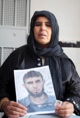 Bilel Kaabi's mother holds up a picture of her son, who was radicalised at a mosque in Tunisia.