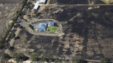 A property lies seemingly untouched, despite the burnt area of land around it.
