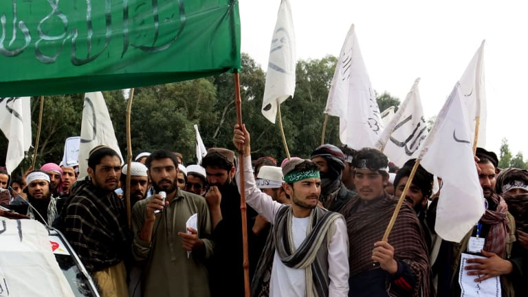 Nangarhar University students raise Taliban and Islamic State flags during a demonstration in Jalalabad earlier this    month.