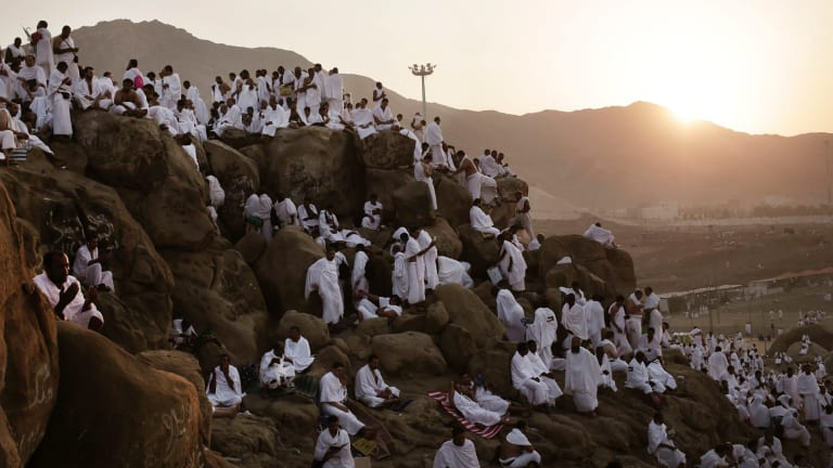 Muslim pilgrims pray on the Mountain of Mercy during The Haj. Mount Arafat, marked by a white pillar, is where Prophet Muhammad is believed to have delivered his last sermon to tens of thousands of followers some 1400 years ago, calling on Muslims to unite.